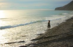 Barefooted girl goes along seashore Royalty Free Stock Image