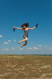 Barefooted girl jumping with her shoes Royalty Free Stock Photo