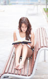 Barefooted girl reading a book. Royalty Free Stock Photography