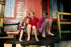 Barefooted girls. Sitting on old wooden stairs royalty free stock photo