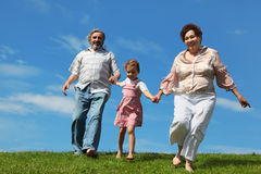 Barefooted little girl and grandparents running Stock Photos