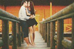 Barefooted love - couple kisses ardently on the wooden bridge Stock Images