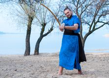 Barefooted man in blue kimono, bun and sticks on head training with sword. And looking at camera on sandy river beach in front of trees and water stock photos