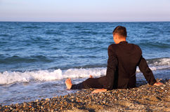 Barefooted man in business suit sits back on coast Royalty Free Stock Image
