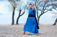 Barefooted man with outstretched hand in blue kimono, bun and sticks on head putting sword behind back. Looking at camera on sandy river beach in front of royalty free stock image