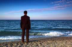 Barefooted man in suit stands back on stone coast Stock Image