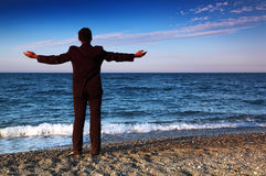 Barefooted man in suit stands back on stone coast Stock Photo