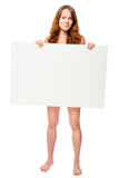 Barefooted naked woman hiding behind a white billboard. In the studio Stock Image