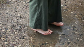 Barefooted in puddle stock video footage