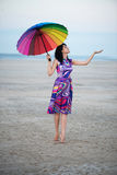 Barefooted woman with colorful umbrella Stock Photo