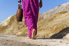 Barefooted woman with a jug. A barefooted woman in ethnical clothes carries in her hand a clay jug stock photo