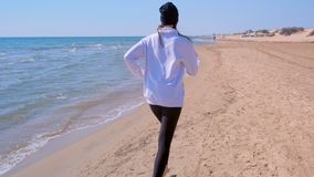 Barefooted woman jogging on sea sand beach back view running training sport. stock video