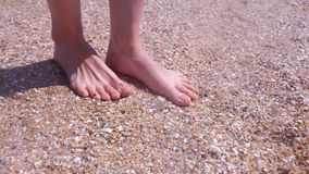 Barefooted girl traveller massaging feet on sandy beach in seashells at seaside. stock video footage