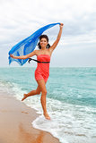 Barefooted woman running. Happy barefooted woman running along the beach royalty free stock images