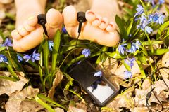 Barefooted woman's feet listening mp3 player Royalty Free Stock Image