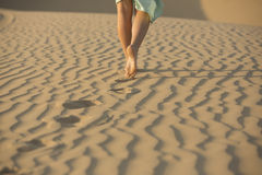 Barefooted woman walks in the sand of desert Royalty Free Stock Photography