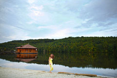 Barefooted woman in yellow dress stands on the lake's shore Stock Images