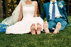 Barefooted young fair-haired bride and her fiance sits on the grass in an exotic park. In a long white dress with a bouquet of flowers in her hands, a walk stock images