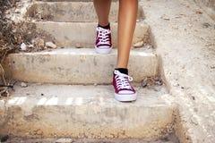 Barelegs com as sapatilhas vermelhas que andam nas escadas Imagem de Stock Royalty Free
