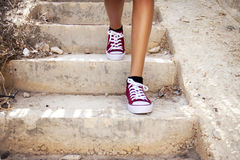 Barelegs con las zapatillas de deporte rojas que caminan en escaleras Imagen de archivo libre de regalías