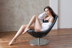 Barelegs female sitting on armchair Royalty Free Stock Photos