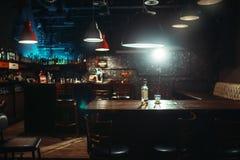 Baren, flaskan av alkohol och exponeringsglas på stång kontrar arkivbild