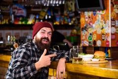Baren kopplar av stället för att ha drinken och koppla av Mannen med skäggdrinköl äter hamburgaremenyn Tyck om mål i bar högt royaltyfria foton