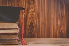 Baret of graduatie GLB op oude boeken stock afbeeldingen