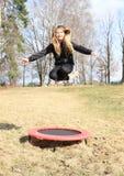 Barfüßig blondes Mädchen, das auf Trampoline springt Stockbild