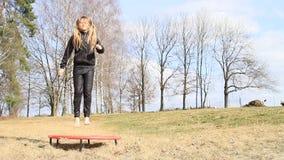 Barfüßig blondes Mädchen, das auf Trampoline springt stock footage