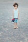 Barfüßig freches kleines Mädchen, das entlang der Kamera entlang der Kamera anstarrt Stockbild