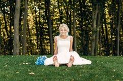 Barfüßig junge blonde Braut sitzt auf dem Gras in einem exotischen Park Stockbilder