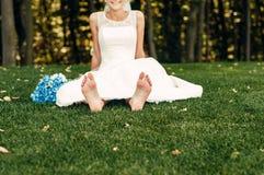 Barfüßig junge blonde Braut sitzt auf dem Gras in einem exotischen Park Lizenzfreie Stockbilder