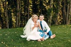 Barfüßig junge blonde Braut und ihr Verlobtes sitzt auf dem Gras in einem exotischen Park Lizenzfreie Stockfotografie
