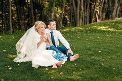 Barfüßig junge blonde Braut und ihr Verlobtes sitzt auf dem Gras in einem exotischen Park Stockbild