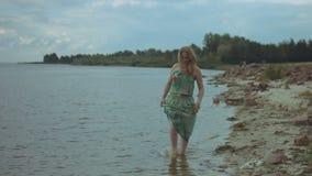 Barfüßig lächelnde Frau, die auf das Seeufer geht stock video