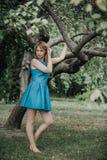 Barfüßig schönes Mädchen im blauen Kleid, das im vorderen Baum steht Stockfoto