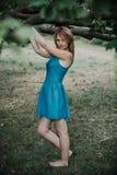 Barfüßig schönes Mädchen im blauen Kleid, das im vorderen Baum steht Lizenzfreies Stockbild