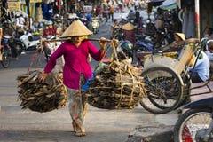 Barfüßig vietnamesische reife Frau in tragendem Holz des konischen asiatischen Hutes in der verkehrsreichen Straße am 13. Februar Lizenzfreie Stockfotos