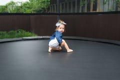 Barfüßigbabyspiele des Active draußen im Spielplatz Porträt des kleinen Mädchens auf einer Trampoline Lizenzfreies Stockfoto