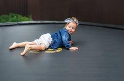 Barfüßigbabyspiele des Active draußen im Spielplatz Porträt des kleinen Mädchens auf einer Trampoline Lizenzfreie Stockbilder