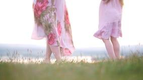 Barfüßigbeine der Mutter und der Tochter, die Spaßtanzen auf dem Gras bei Sommersonnenuntergang haben stock video footage