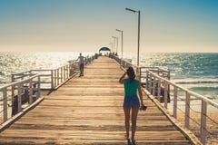 Barfüßigfrau, die entlang den Pier geht Stockfotografie