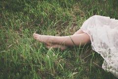Barfüßigfrauenbeine auf Gras stockfoto