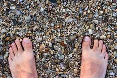Barfüßigmann, der auf Rocky Beach steht Lizenzfreies Stockbild