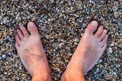 Barfüßigmann, der auf Rocky Beach steht Lizenzfreie Stockfotos