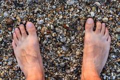 Barfüßigmann, der auf Rocky Beach steht Stockbild
