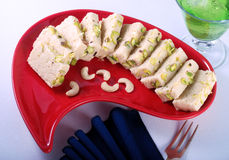 Barfi in Red Dish. Mouth watering sweet treat of Asia Stock Photos