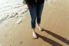 Barfoot di camminata della donna alla spiaggia e schiuma avere alle sue dita del piede immagine stock libera da diritti
