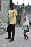 Barfota afrikanska barn promenerar fiskeläget, Zanzib Royaltyfri Bild